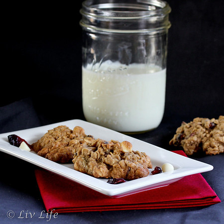 Quinoa Oatmeal Cookies with Cranberries and White Chocoalte, photography on a black background.  Includes a red napkin