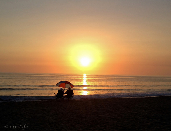 couple sititng on the beach with unbrella watching San Diego Sunset