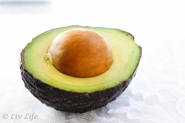 Half of an avocado photographed on white